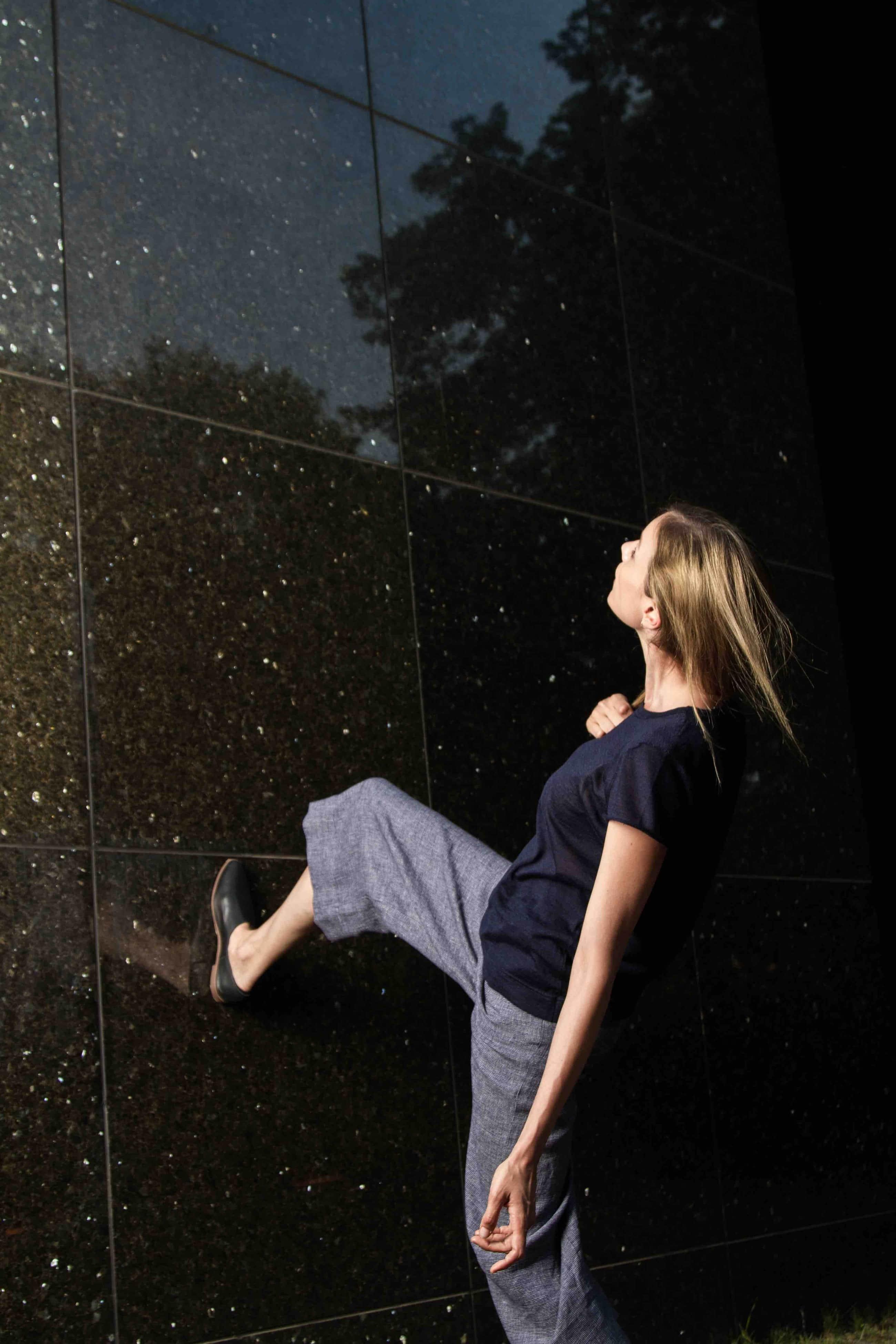 Woman walking up a wall.