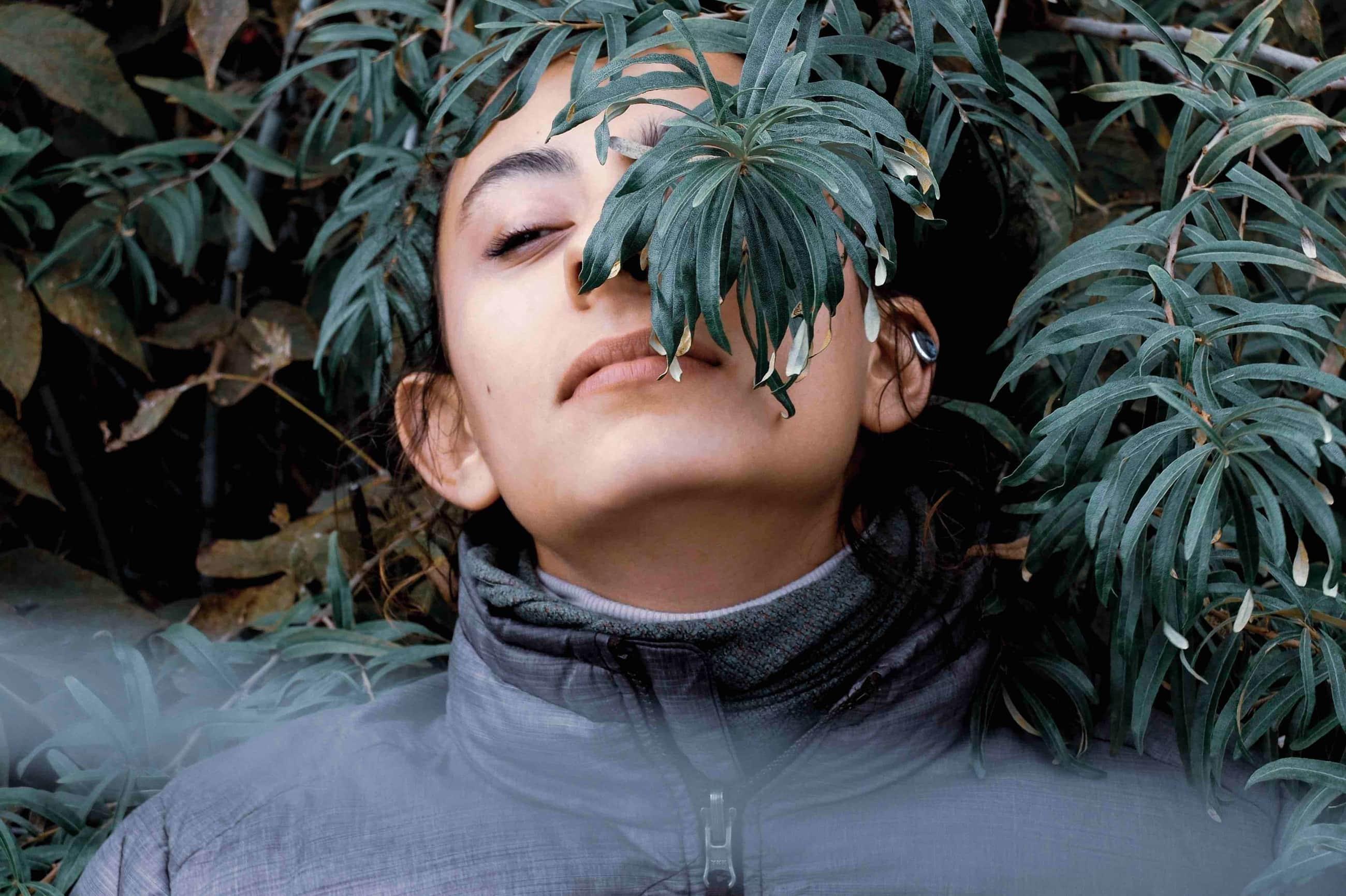 Woman sitting in plants.