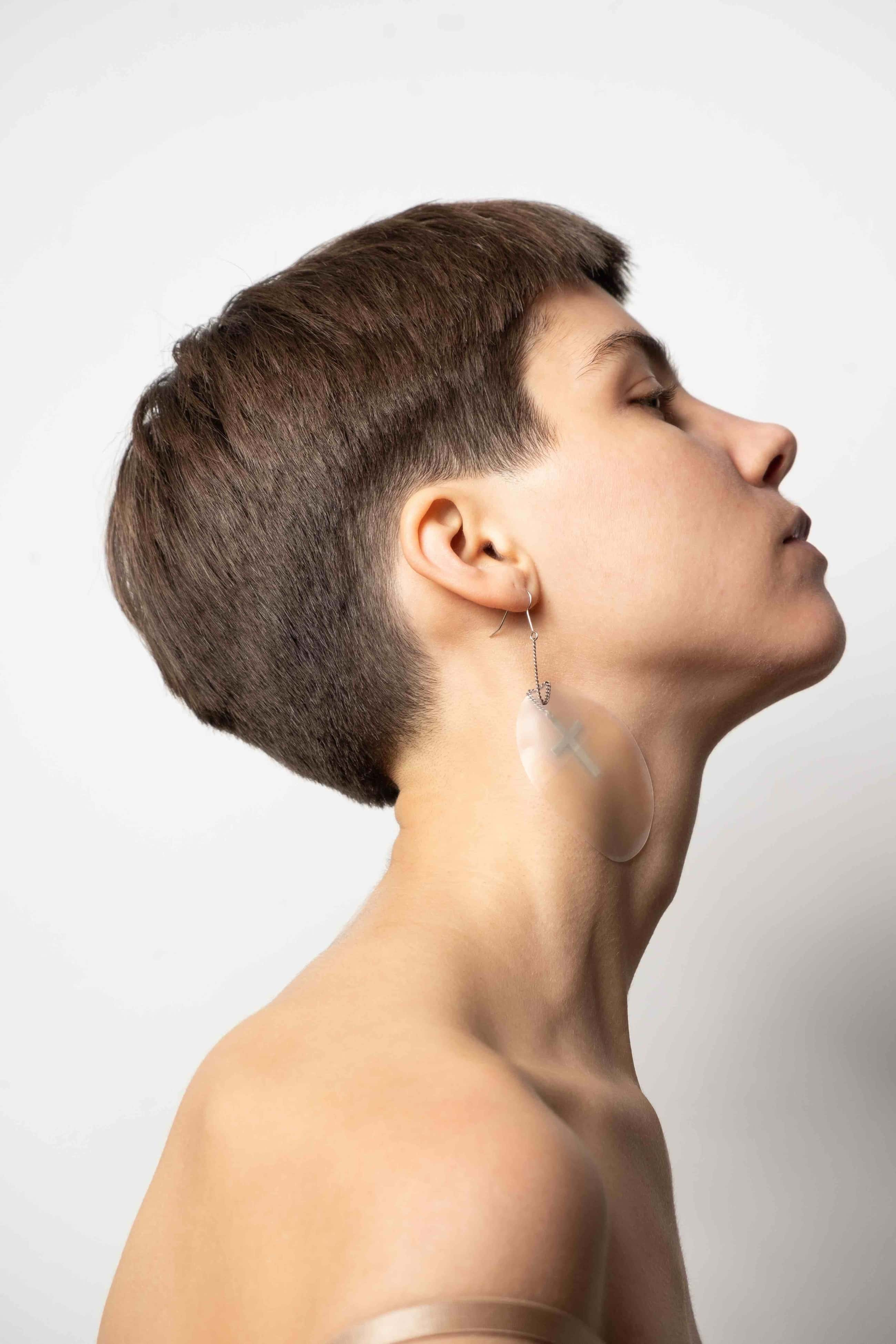 Model photographed from the side with art jewelry.