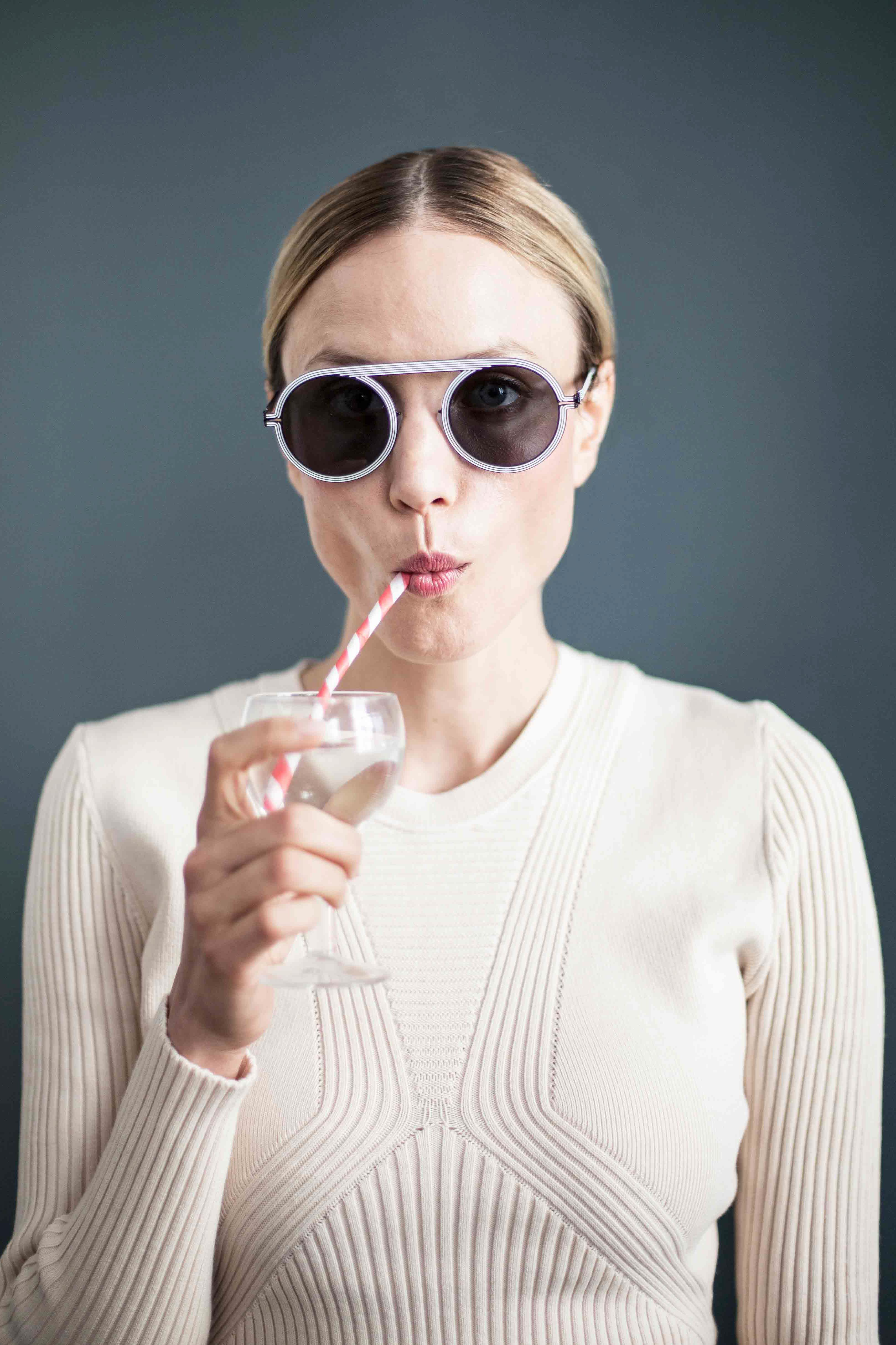 Woman drinking water with straw.
