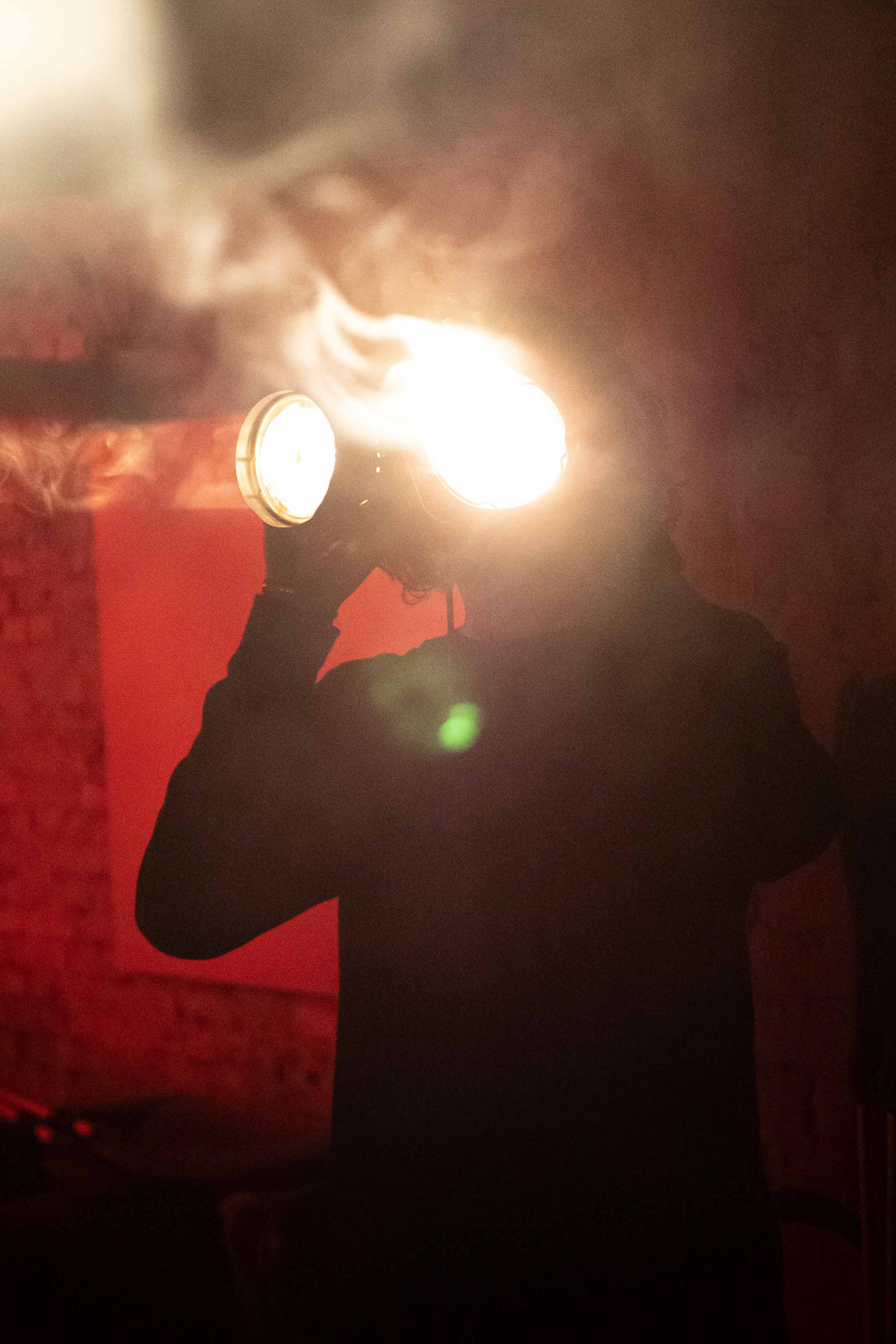 Man holding lights in front of face.