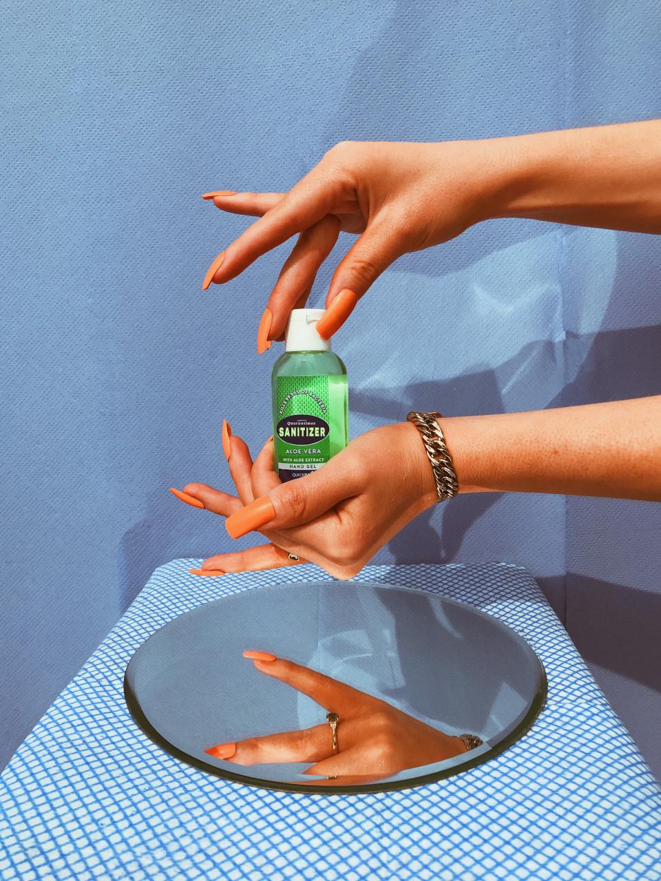 Feminine hands holding a bottle of hand sanatizer.