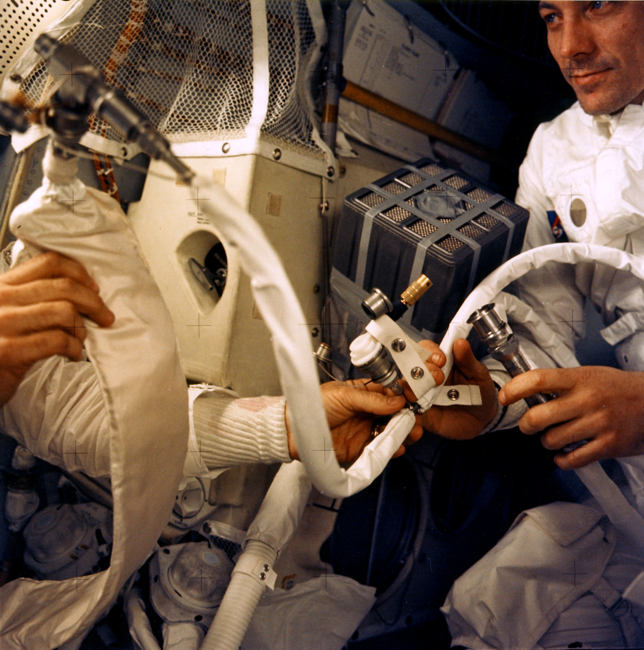 Crew from the Apollo 13 mission next to their jerry-rigged life-support system on their trip back to Earth