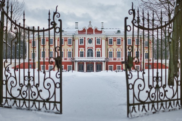 a palace behind some old, slightly ajar iron gates