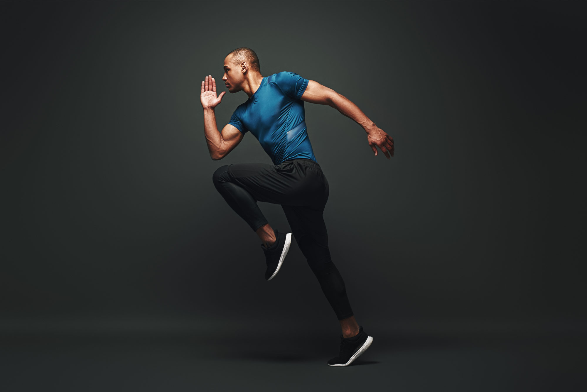 Athletic black man running, wearing a blue top, black joggers and black trainers.