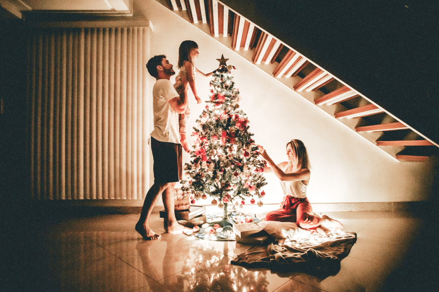 young family decorates christmas tree together