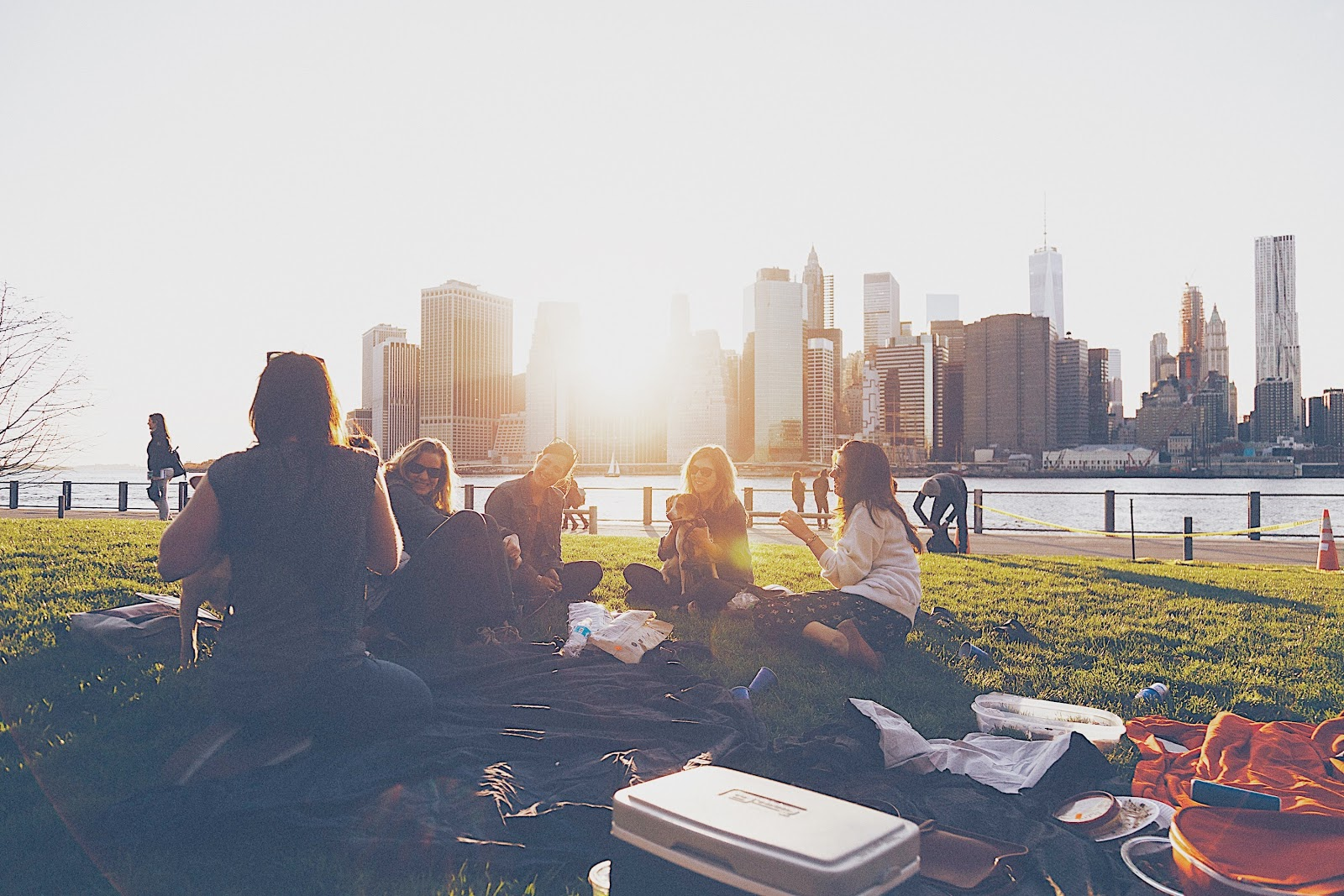A group of 6 friends share a sunset picnic together in a grassy park across the river from a large city with sunset shining through a skyline filled with tall high rise buildings