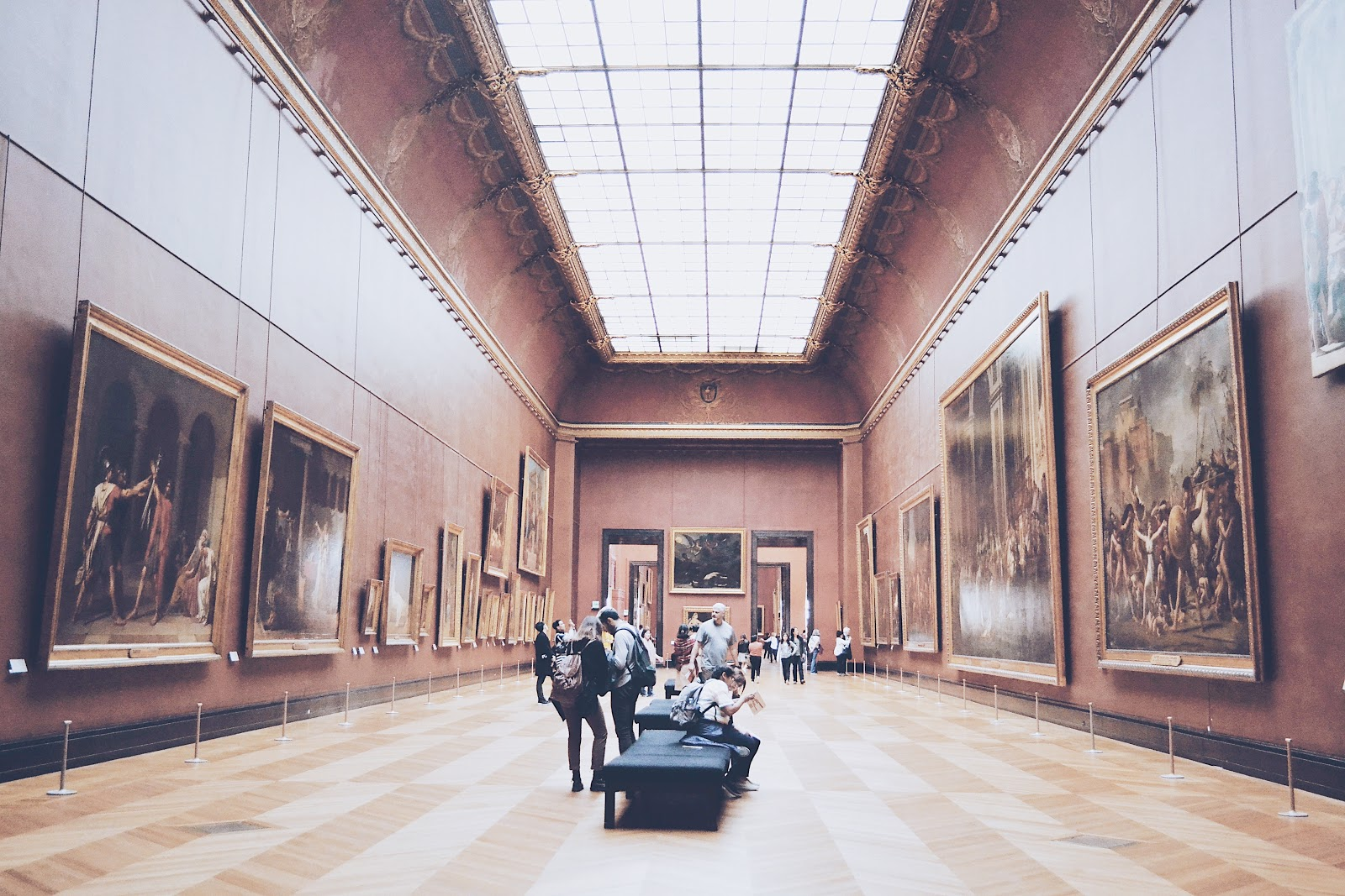 people stand and sit gathered on benches within a long museum hallway with tall walls lined with large artwork