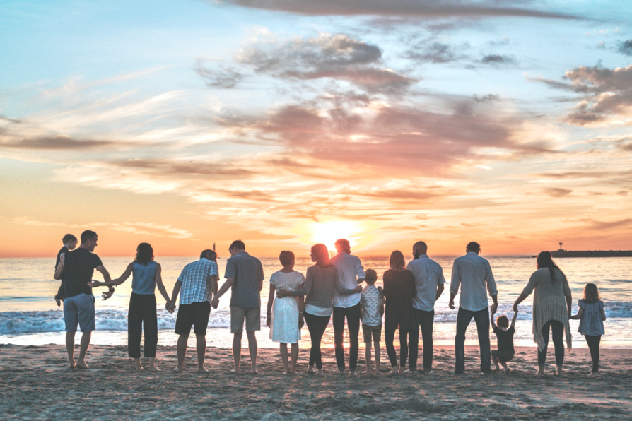 Happy family gathers near ocean in memory of loved one