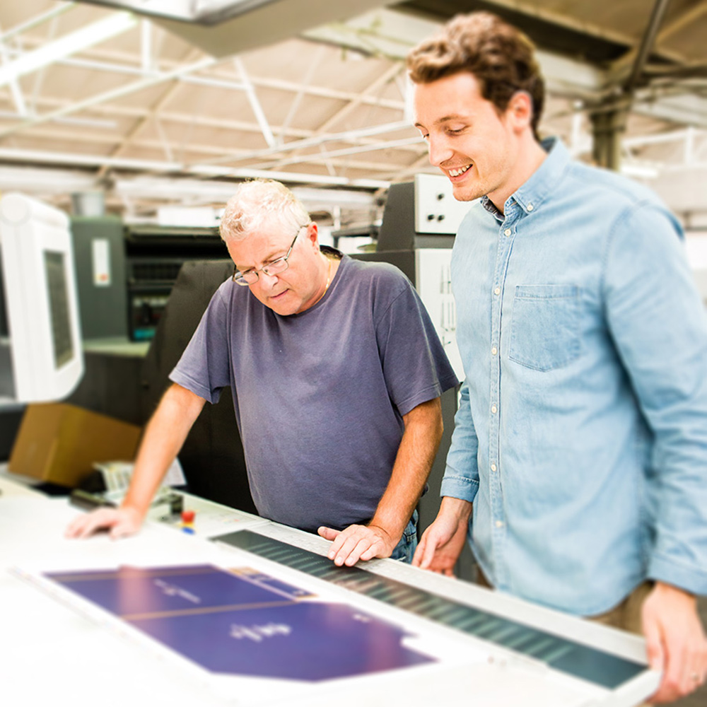 Design and printer reviewing packaging production on printing press