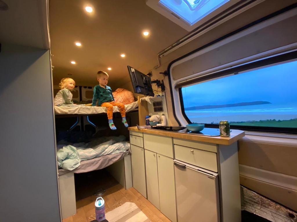 children watching tv in a campervan conversion