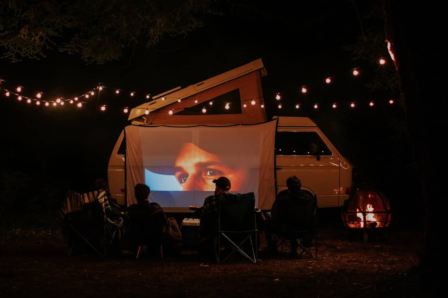 people sat watching a movie projected onto a campervan
