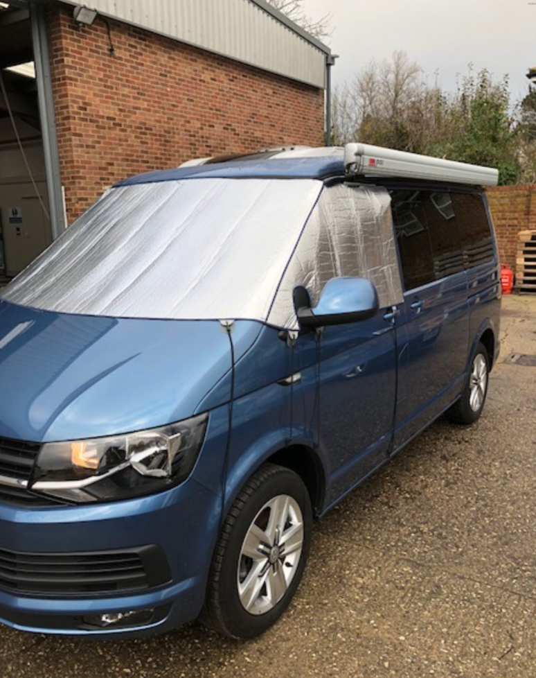 a blue VW transporter covered in a silver thermal blanket