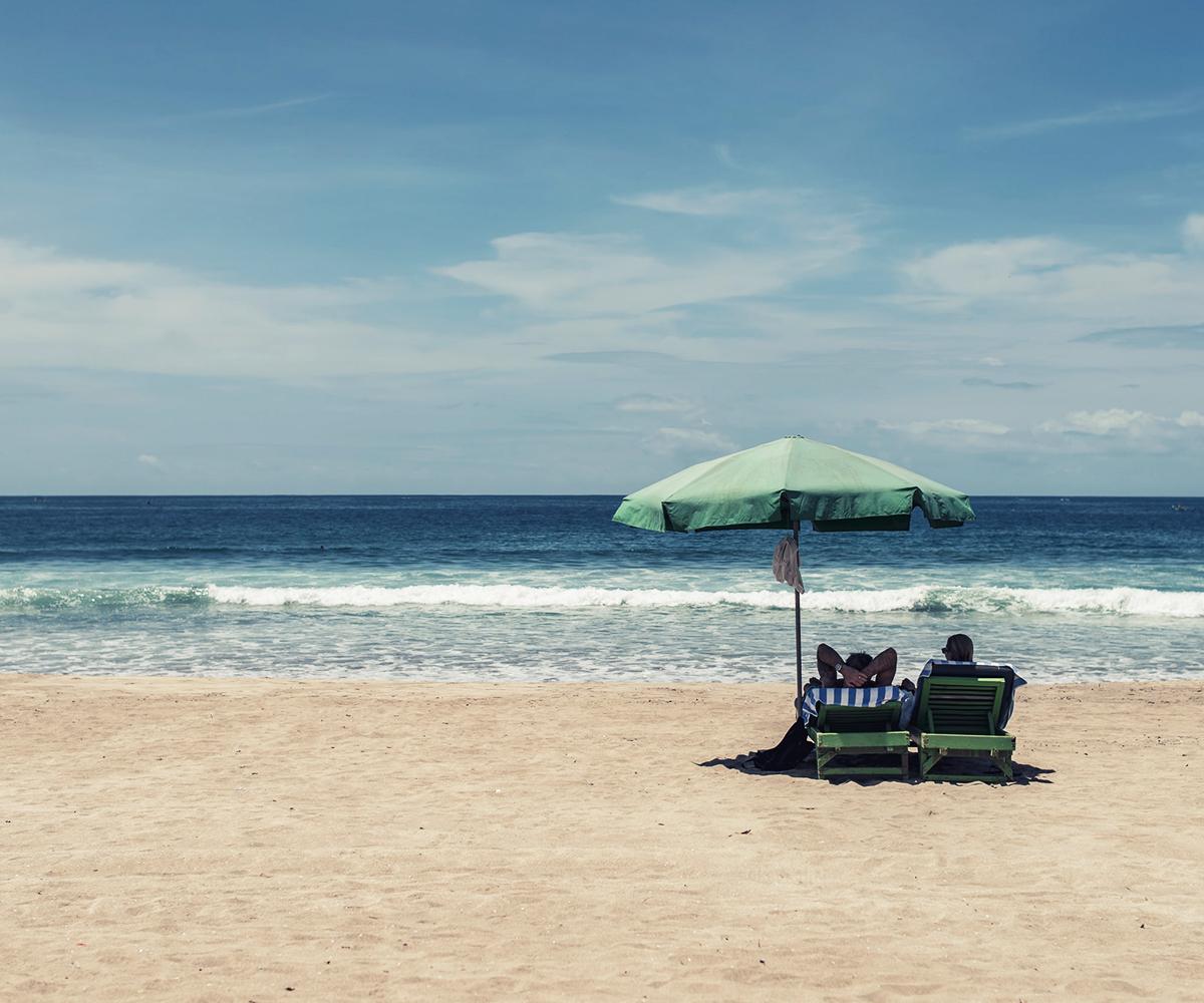 beachgoers relaxing in ocean city maryland under beach umbrella
