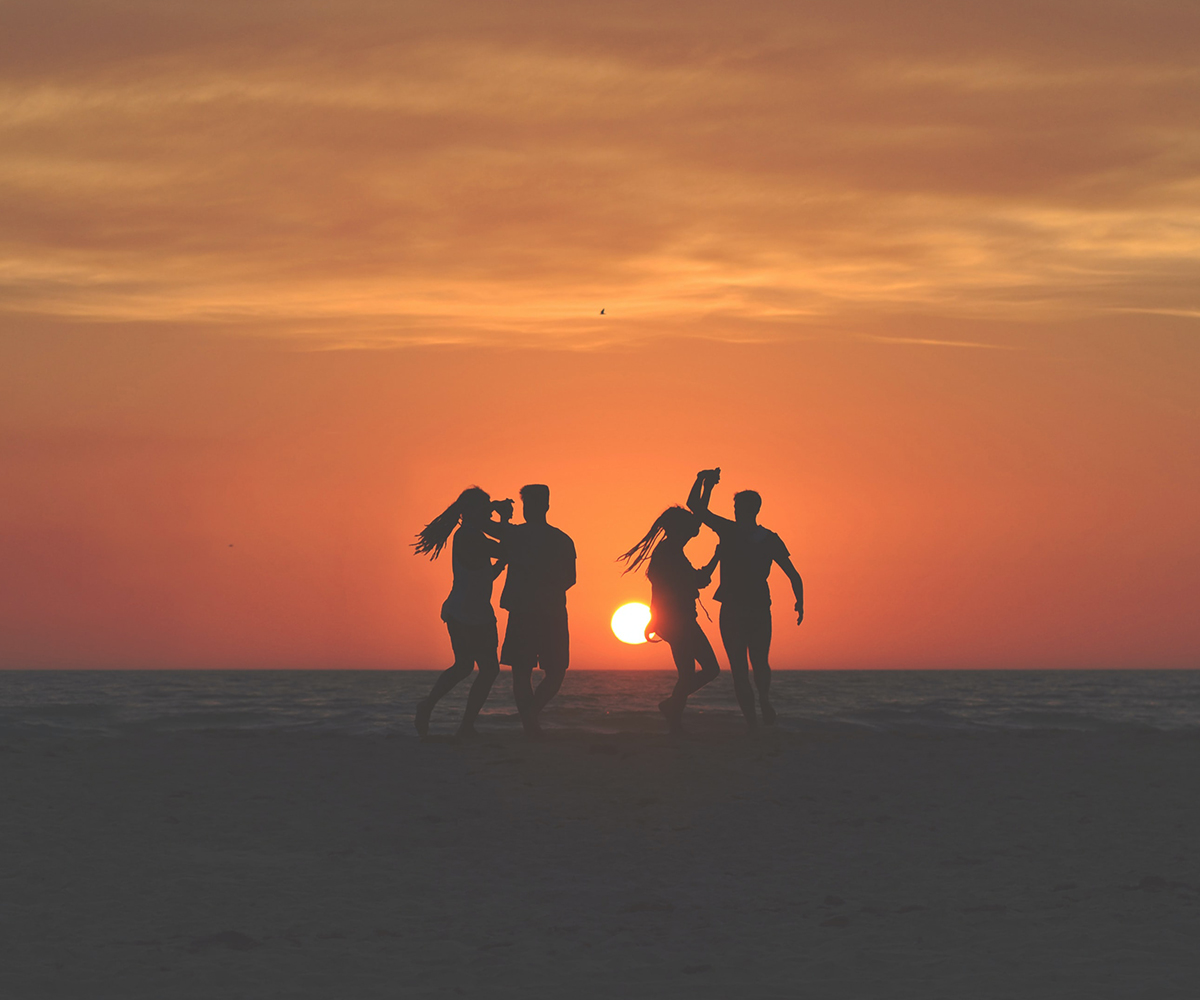 four people party on ocean city maryland beach at sunset