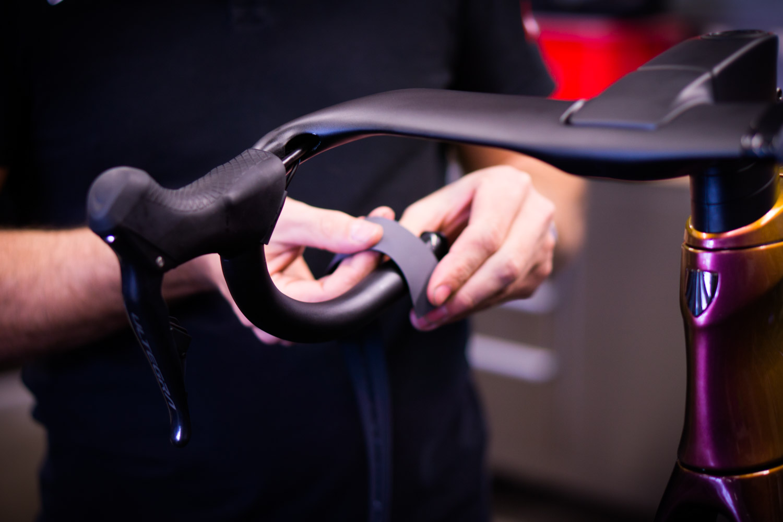Bike mechanic attaching bar tape to Madone at CYCO bike workshop