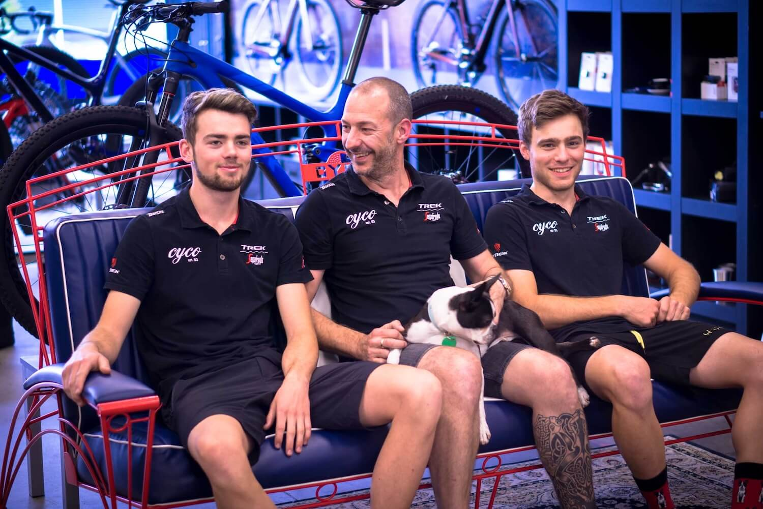 Three employees of bike shop sitting on sofa smiling