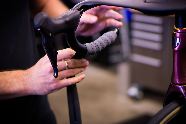Bike mechanic wrapping new handlebar tape on Trek Madone