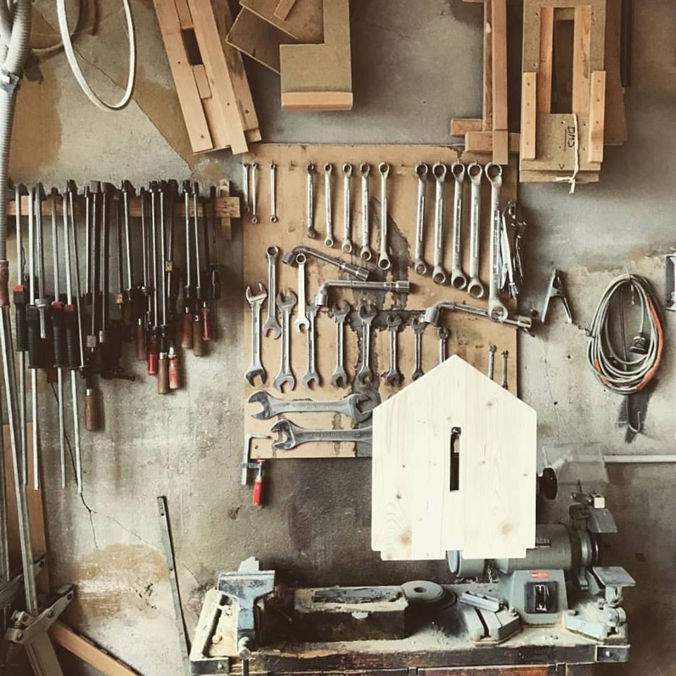 Mur d'outils dans les ateliers Copacabanon dans le Jura. Logo Copacabanon en bois.