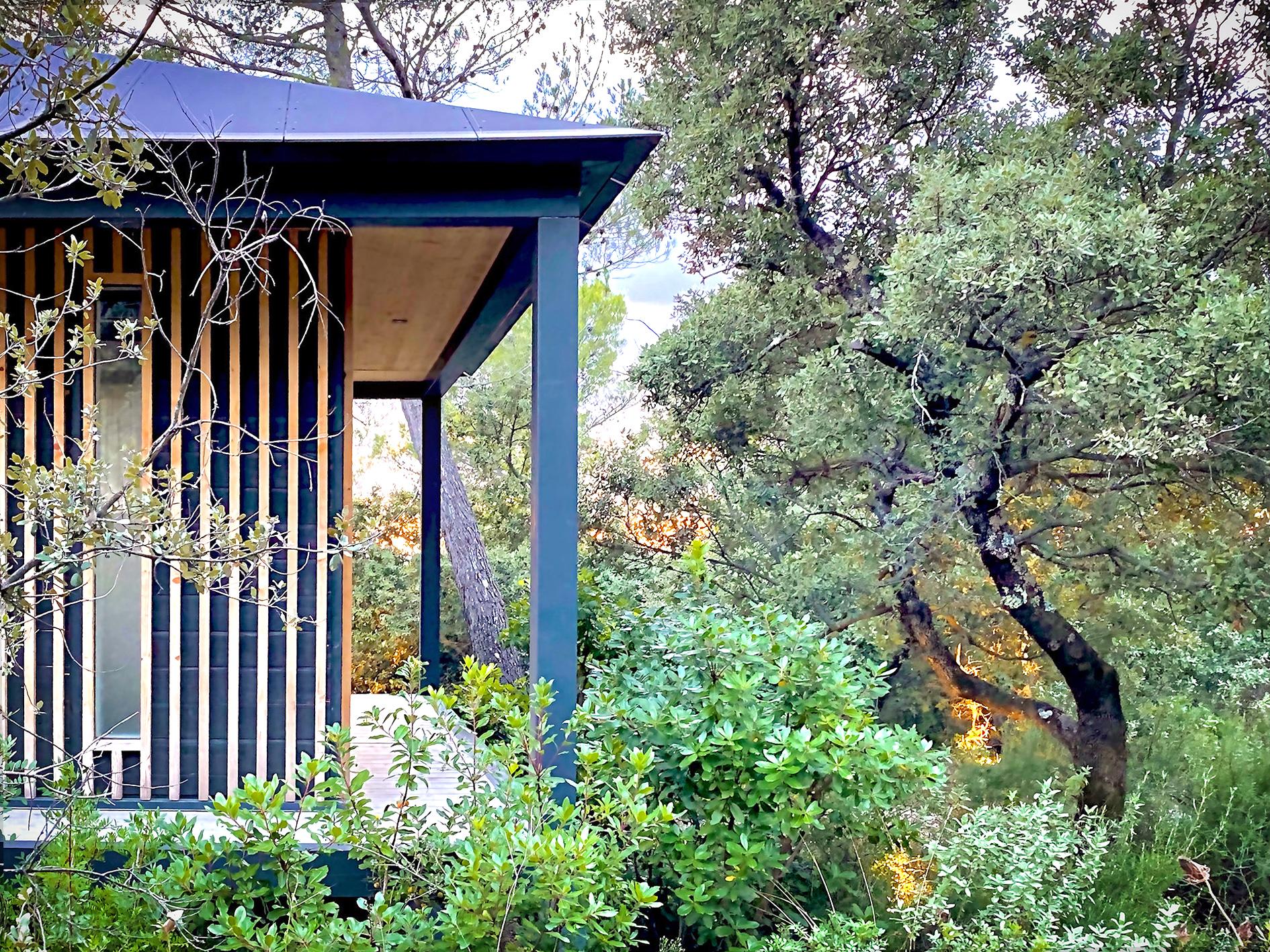 Cabane Kobé au milieu des arbres, en osmose avec la nature.