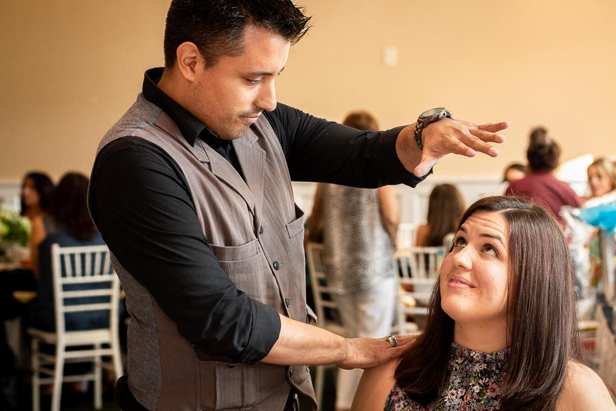 magician actor richard torres hypnotizing a woman holding his left hand above her head