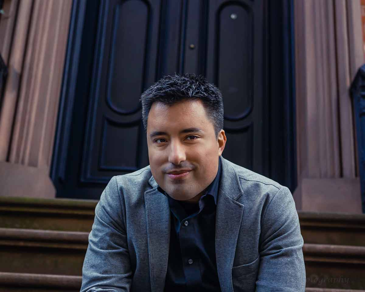 actor magician richard torres sitting on steps in gray blazer