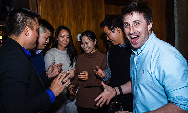 actor magician richard torres  performing card tricks to amazed group surprised male stares in camera