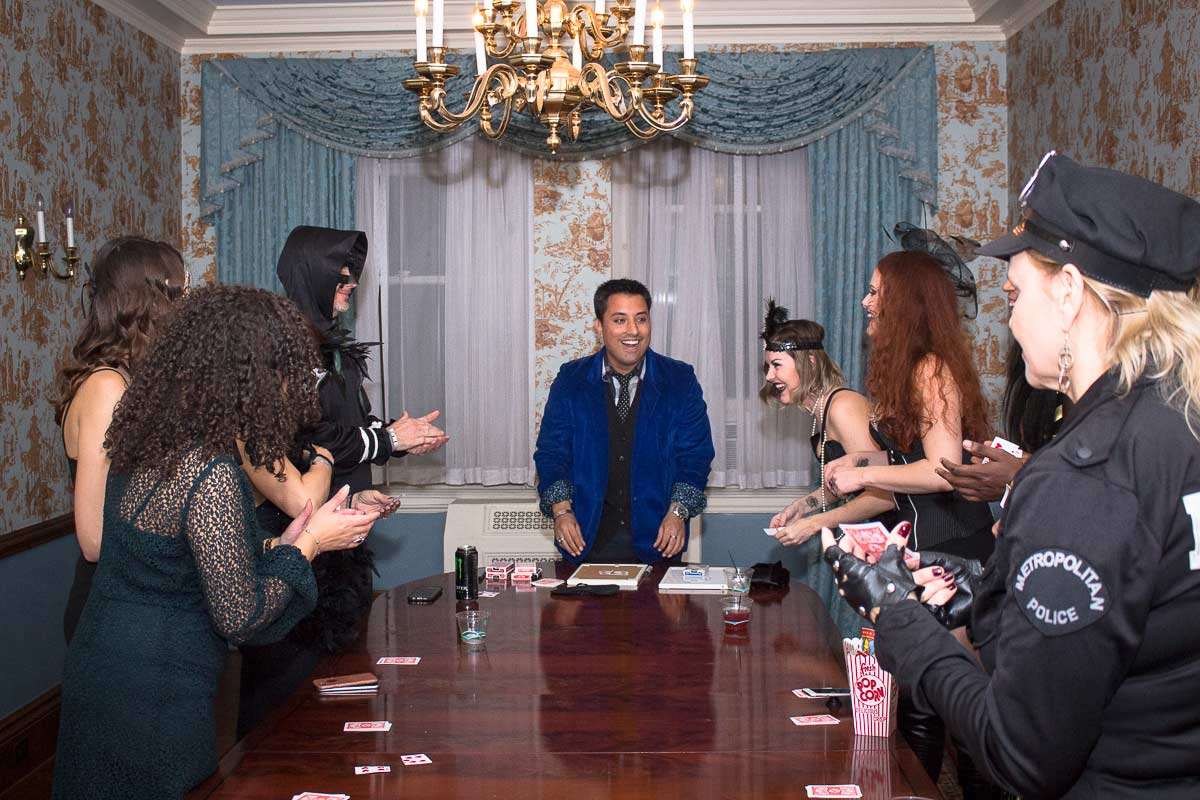 centered a magician in blue blazer and guests laughing surrounding a table watching a trick