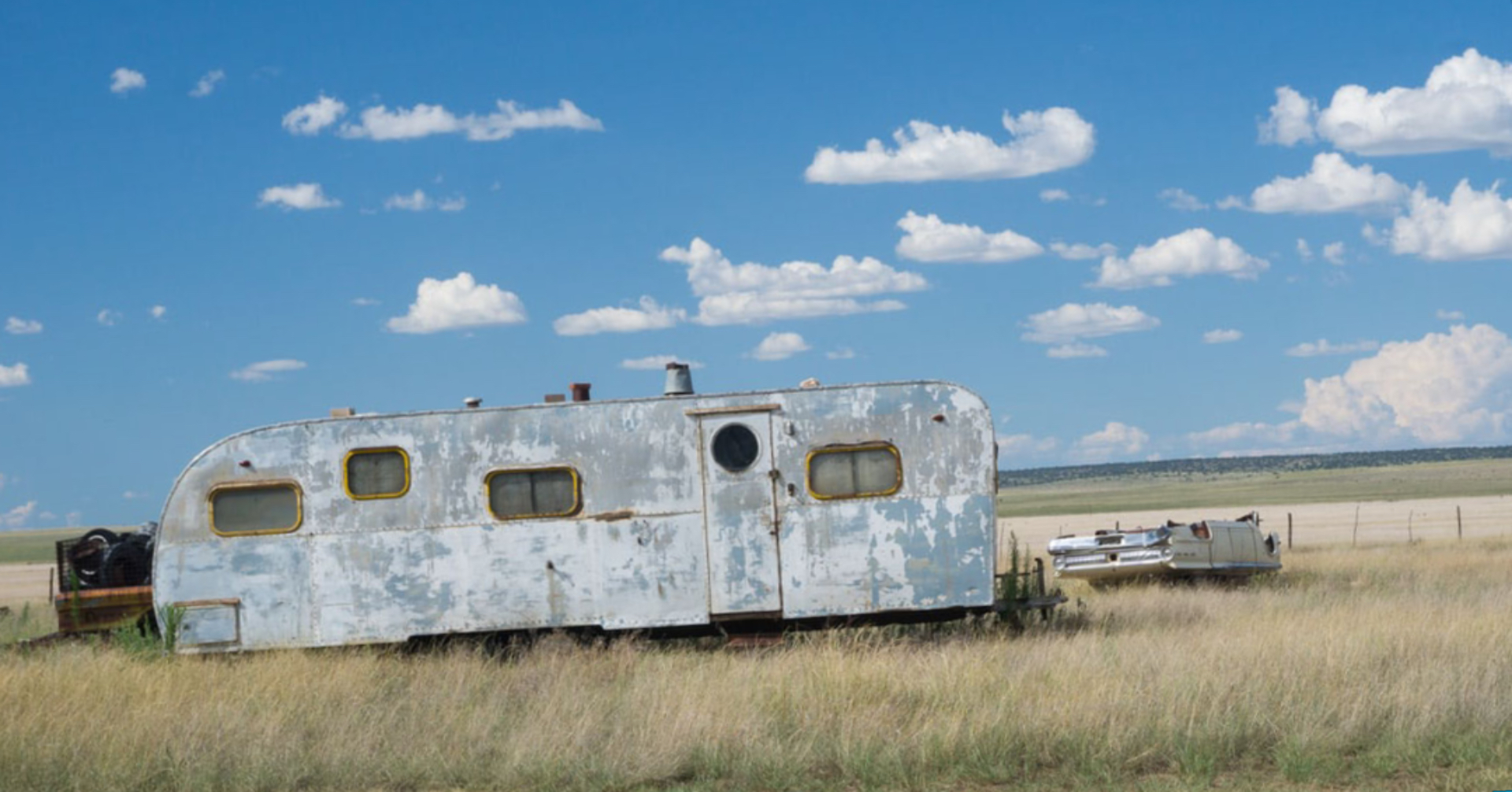 Abandoned travel trailer left in a field to rot.