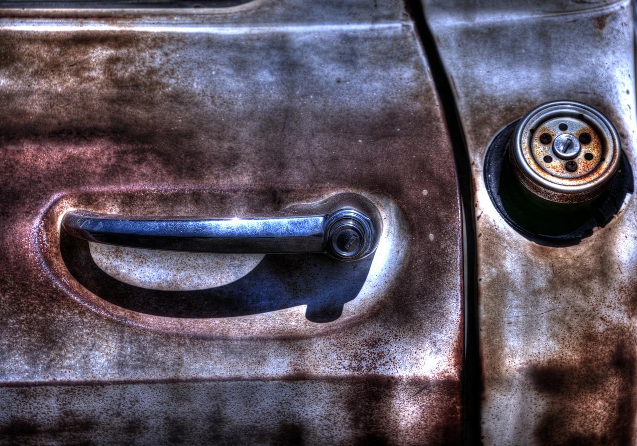 Rusty door handle with old gas cap