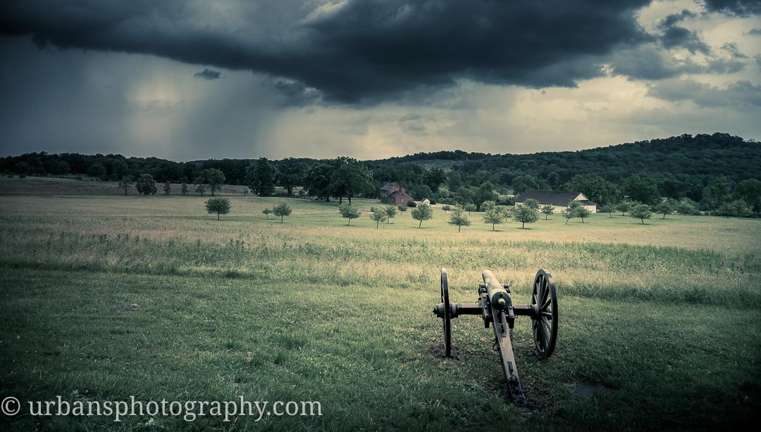A summer storm over the Bushman farm in Gettysburg with a canon looking on.