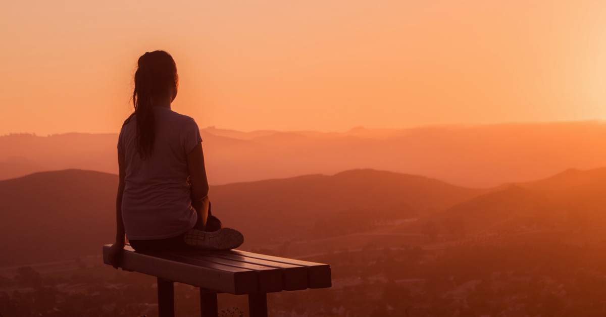 Meditation scene on a mountain top with a sunset.