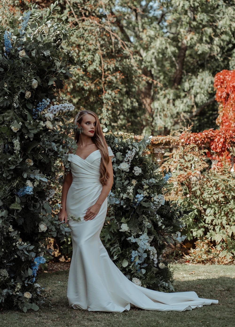 Open flower arch and bride in Enzoani Marla dress