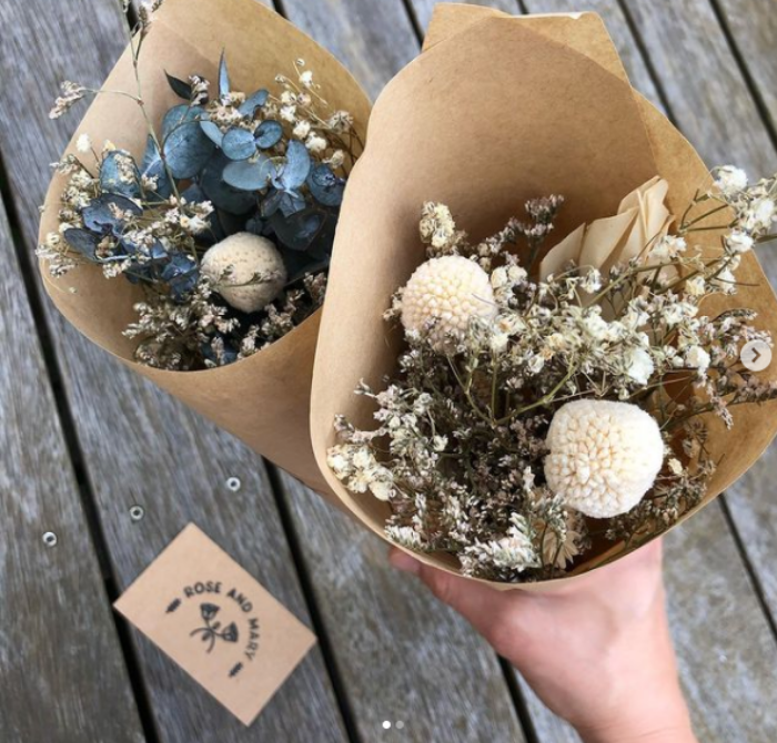 A photograph of dried flower bouquets next to a branded 'Rose & Mary' business card with logo