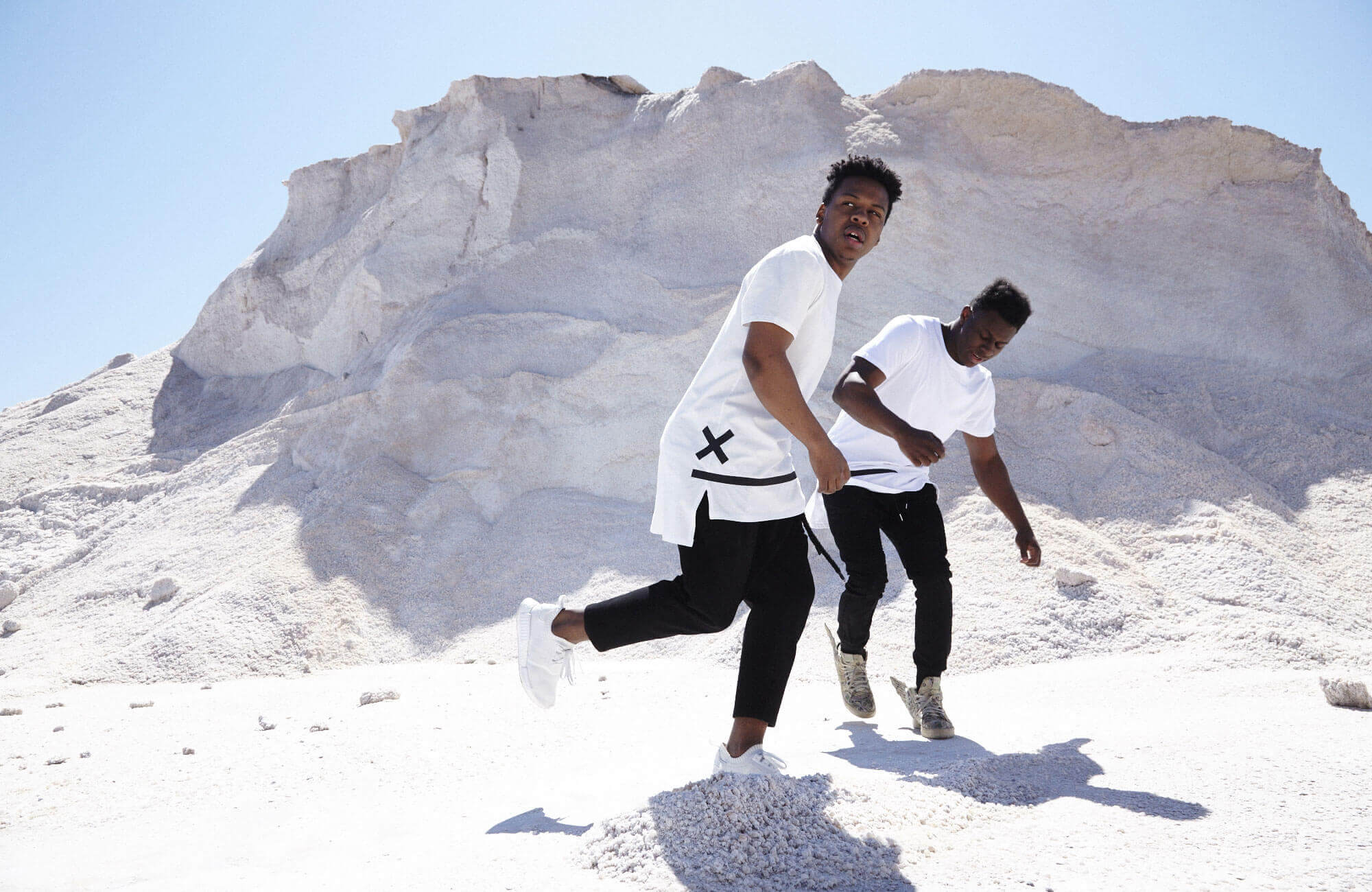 Two men dancing in a gravelpit wearing clothes from streetwear brand unsignd