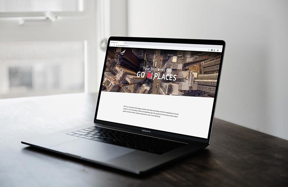 open macbook pro on a wooden desk showing WIP's website