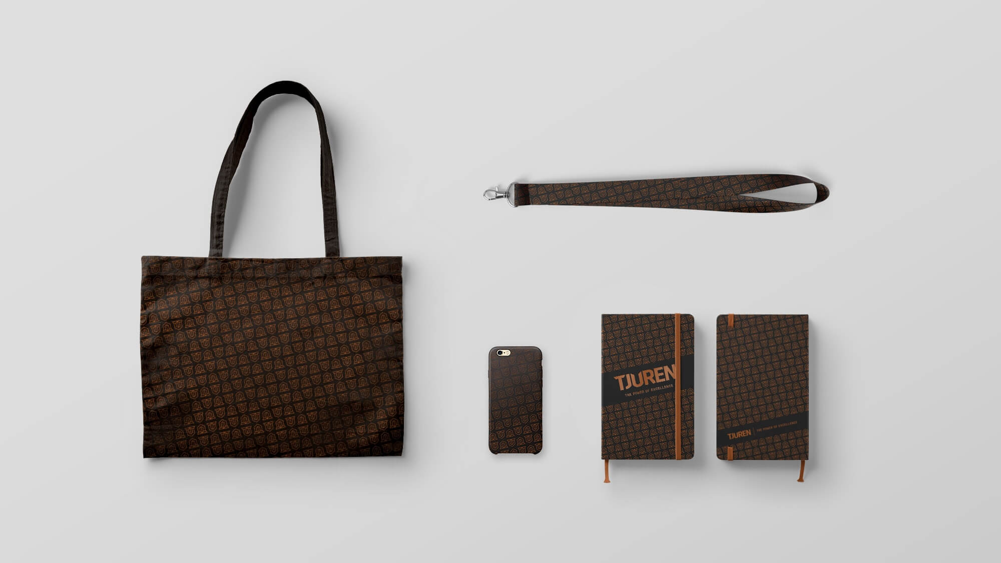 a lanyard, a totebag, a phonecase and a notebook on a flat surface, all with tjurens branding.