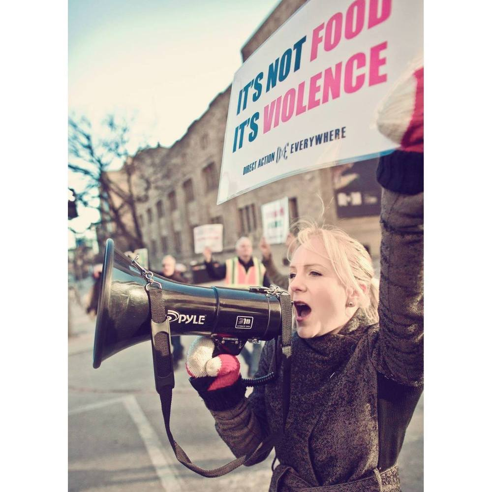 DxE Toronto activist Jenny Henry speaks into a megaphone powerfully for animals.