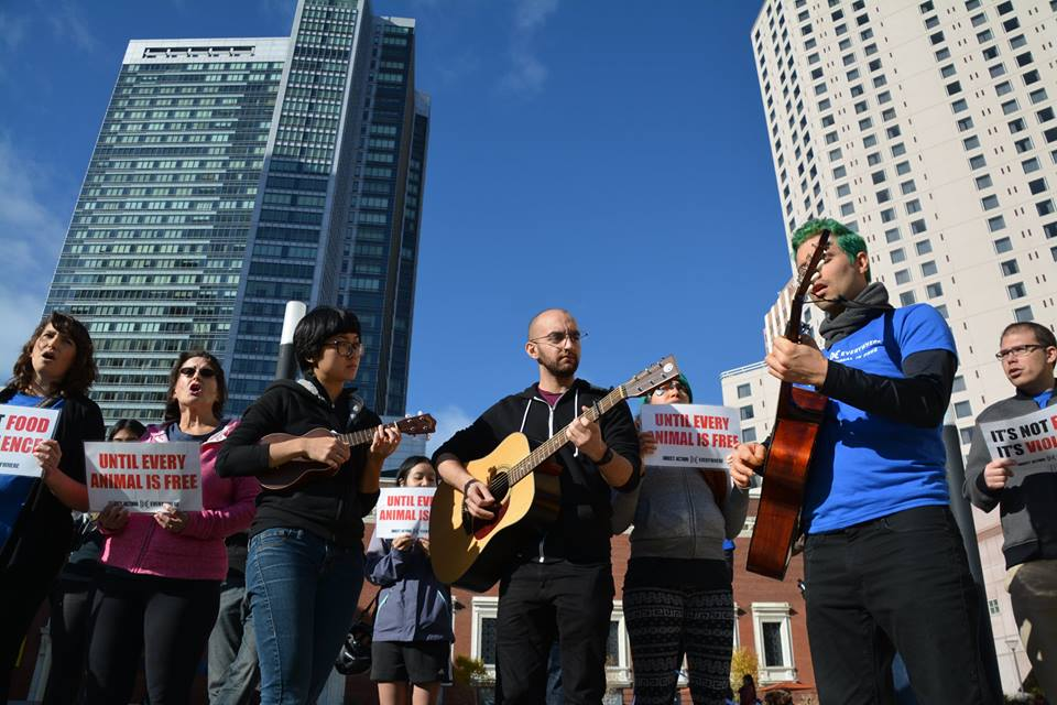Samer, in the middle, plays guitar at a musical demonstration