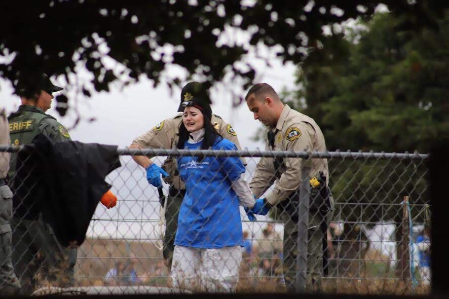 DxE activist Rachel Ziegler is arrested after having a bird ripped from her arms by police.