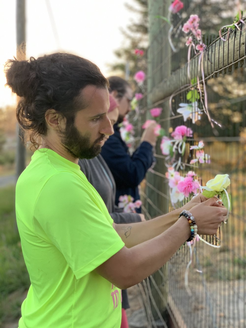 An activist arrested at the farm last month ties a flower to the gate outside Reichardt Duck Farm in Petaluma