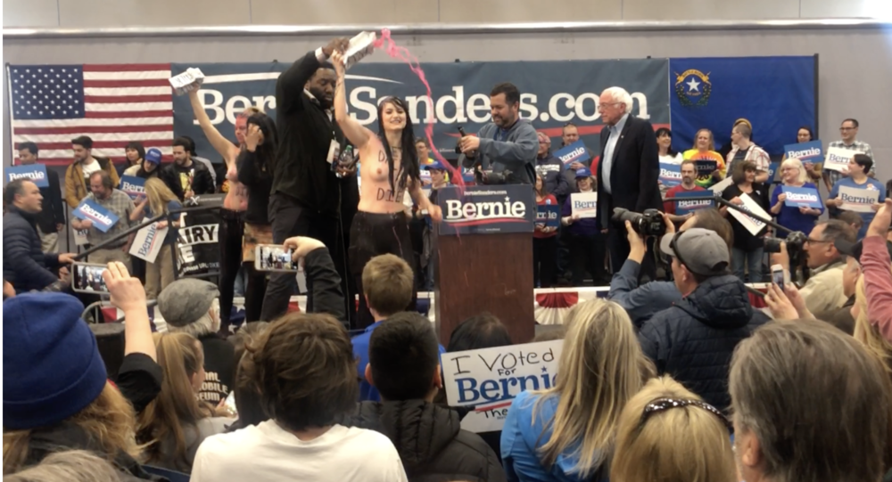 Rachel Ziegler (center) disrupting Bernie Sanders' speech (Credit: Direct Action Everywhere)