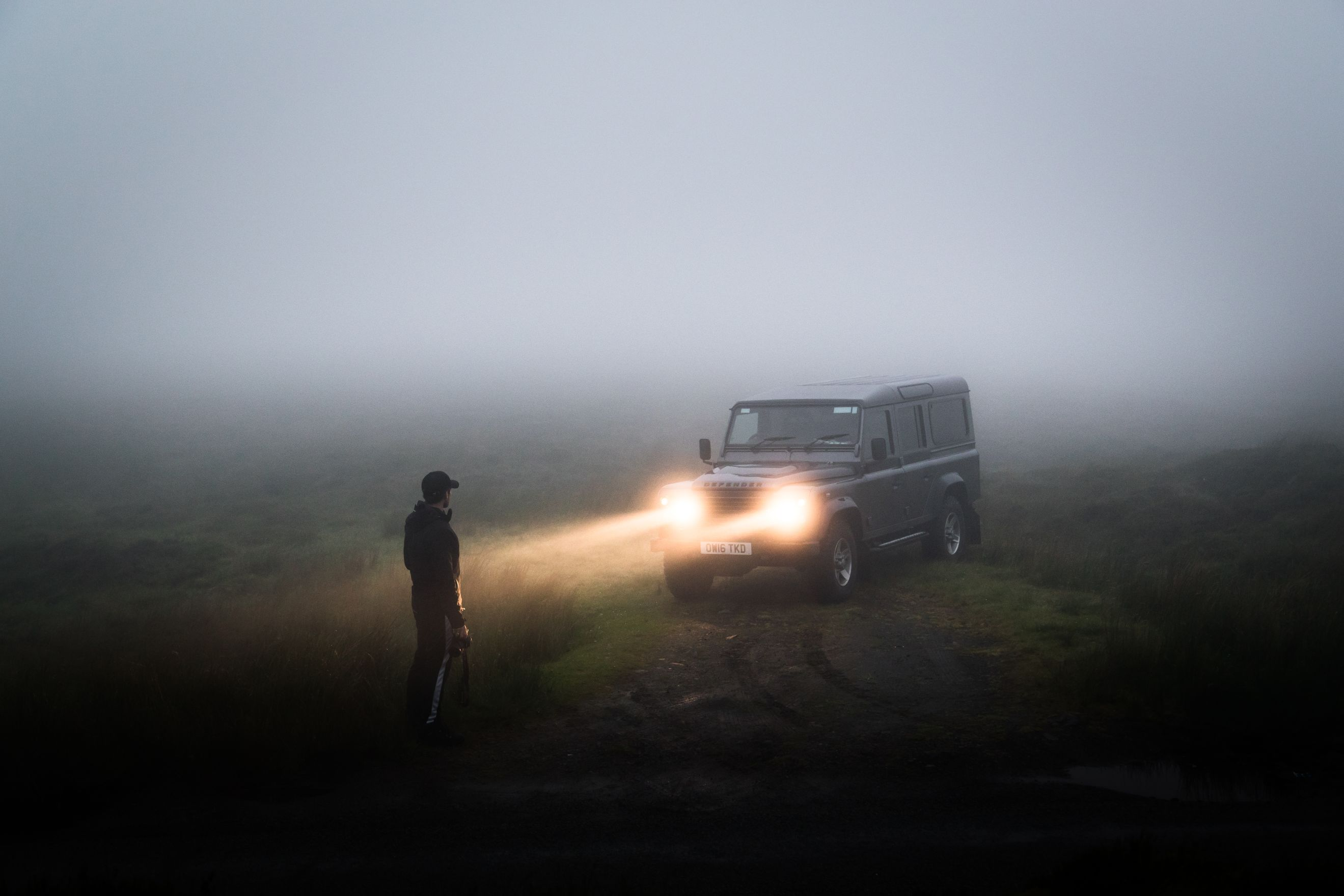 Car shining its lights onto a man standing amongst the mist.
