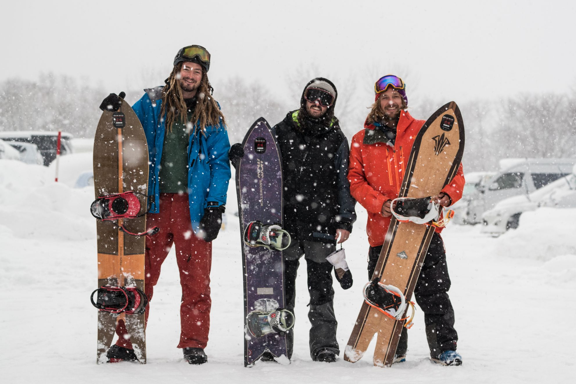 Three snowboarders stand together holding their boards.