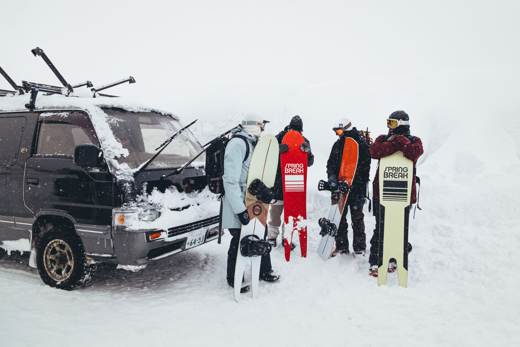 Snowboarders stand in front of car holding their boards.