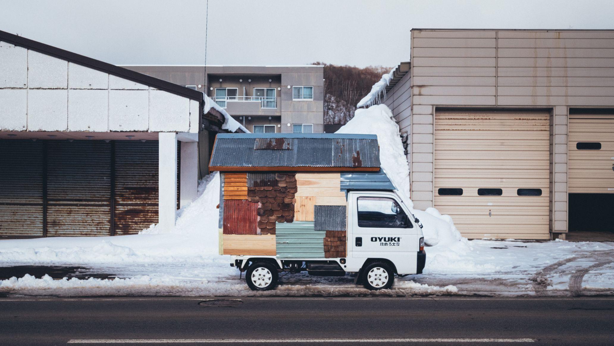 Small camper van in front of industrial buildings.