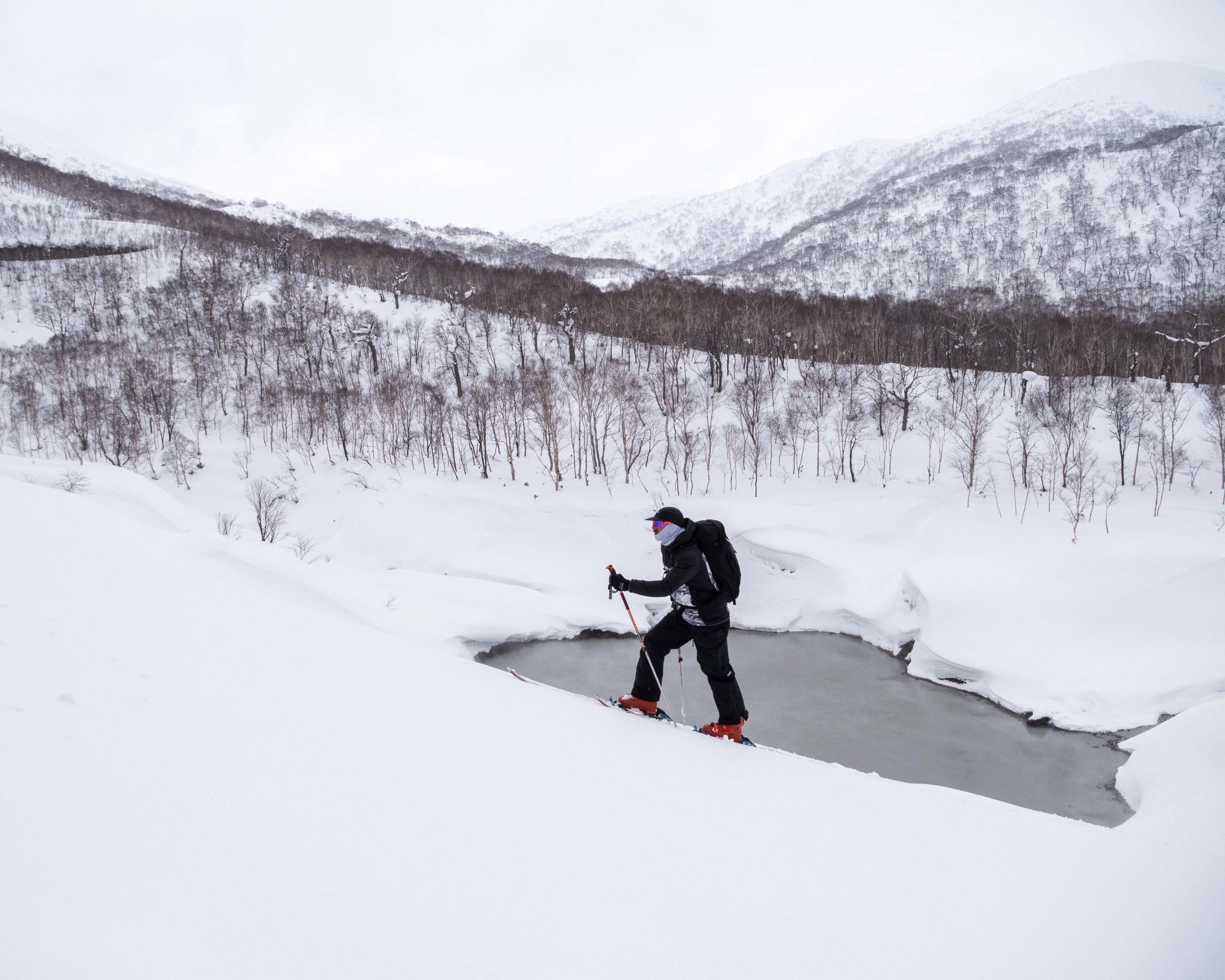 Man snowshoeing up bank with frozen lake in the background.