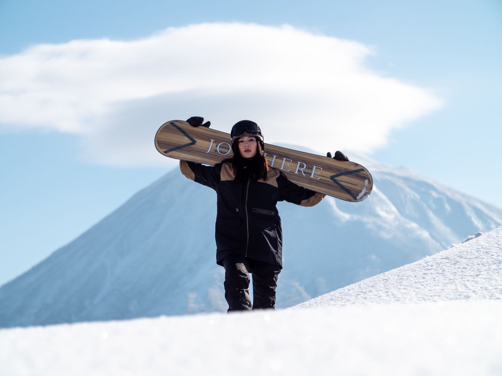 Women holding a snowboard in her hands with a mountain in the background.