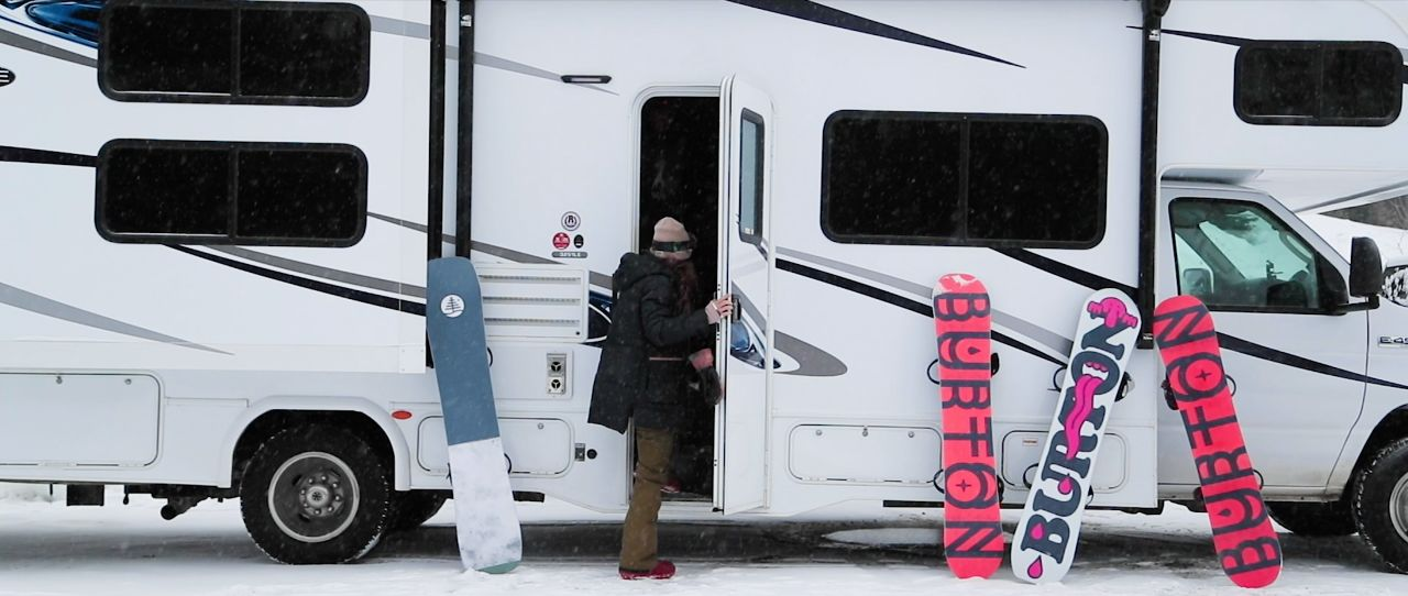 A women stands in front of RV with 3 snowboards.