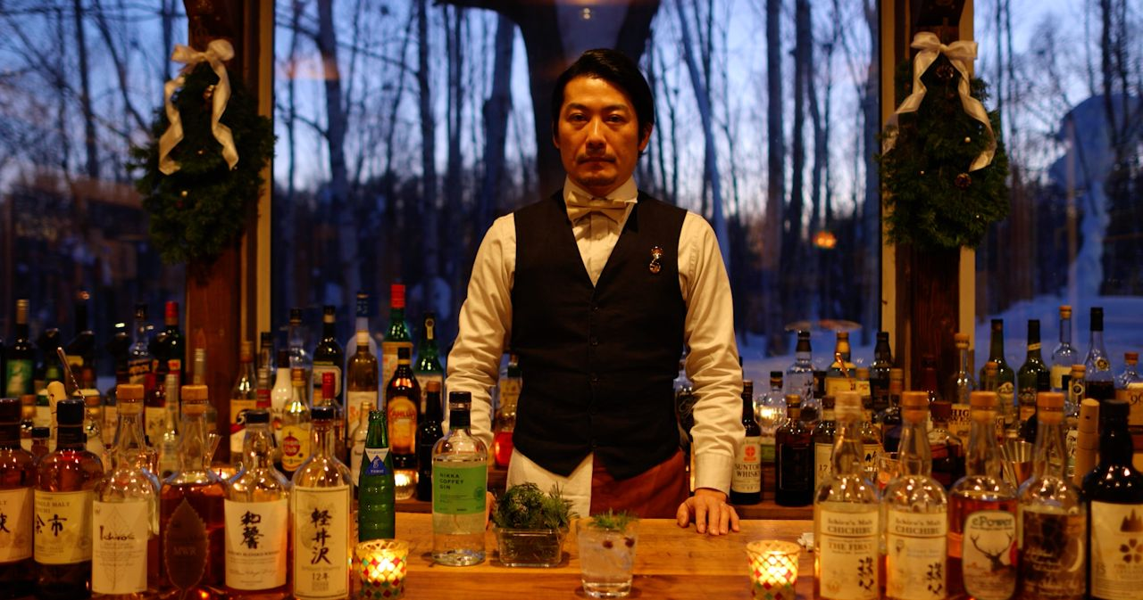 Bartender standing behind counter.